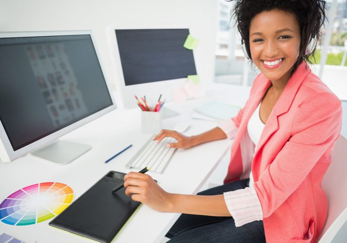 Portrait of a casual female photo editor using computer in a bright office